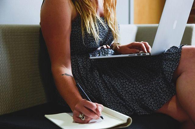 mujer-escribiendo-con-cuaderno-y-portátil