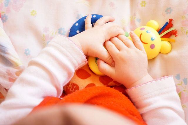 manos-de-bebé-con-juguete-amarillo