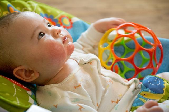 bebé-acostado-junto-a-juguete