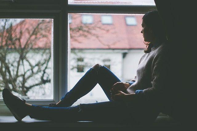 mujer-sentada-cerca-de-una-ventana
